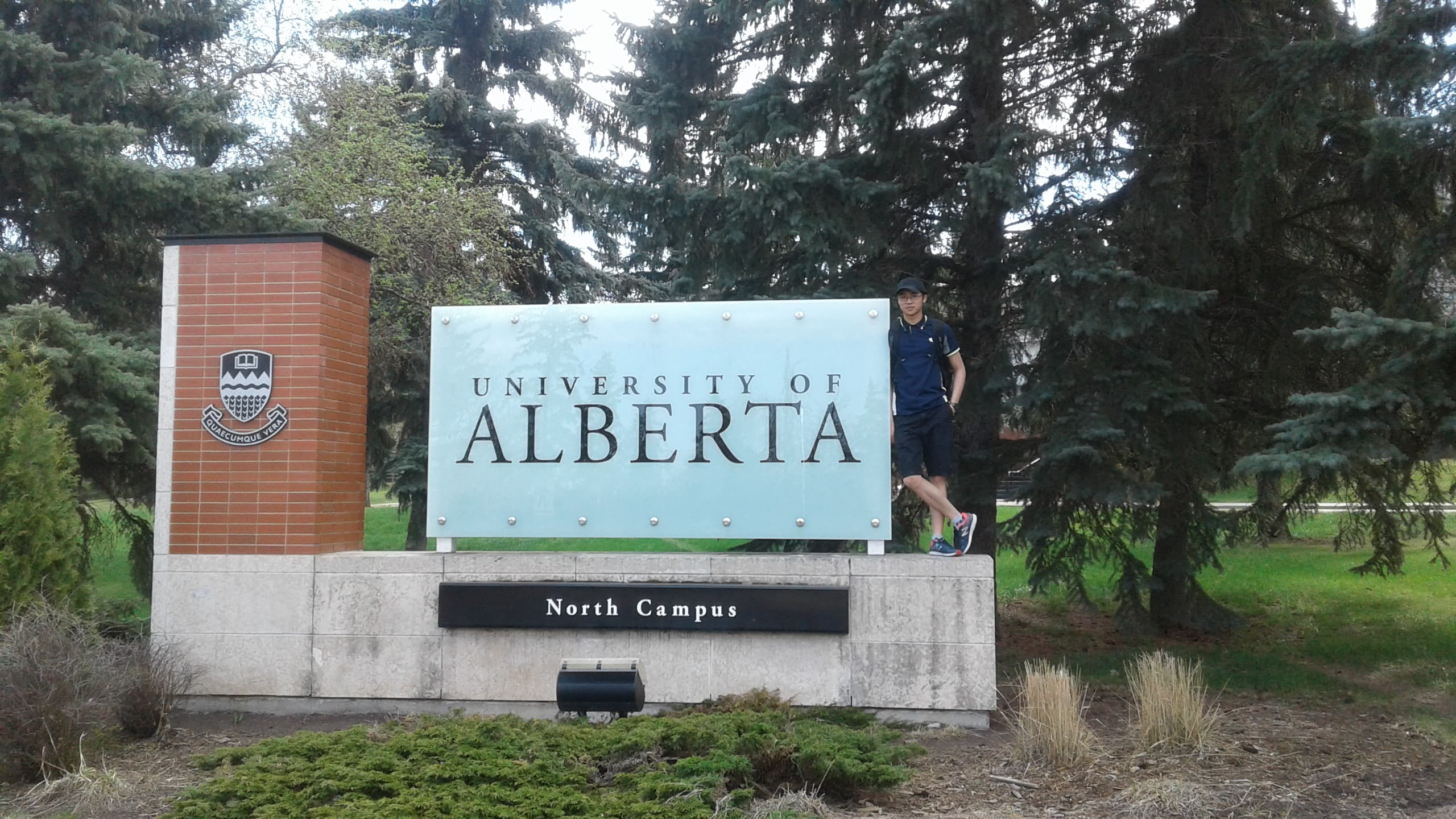 man standing with university of alberta sign