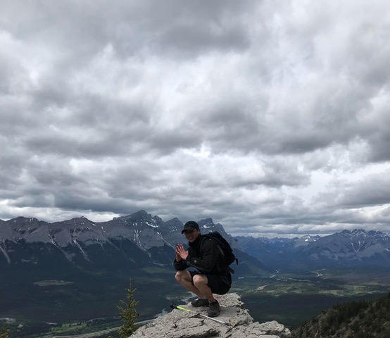 man posing right at the top of the mountain with grey sky above