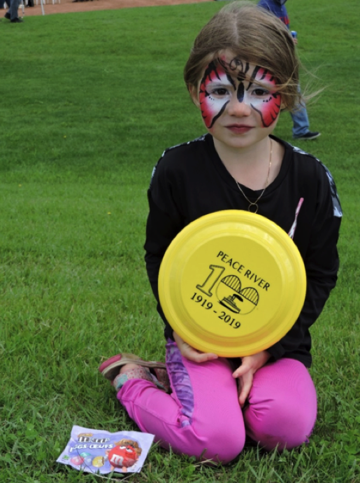 face painted child sitting with frisbee