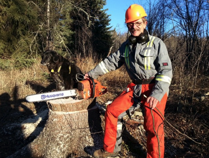 man standing by tree stub with chainsaw