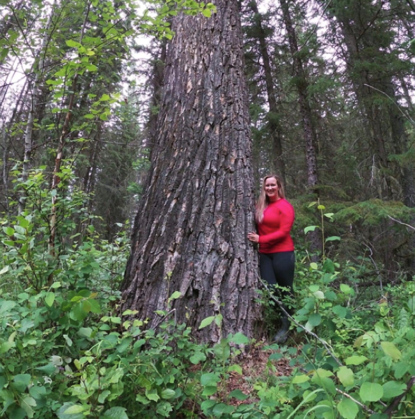 woman standing next to very large tree