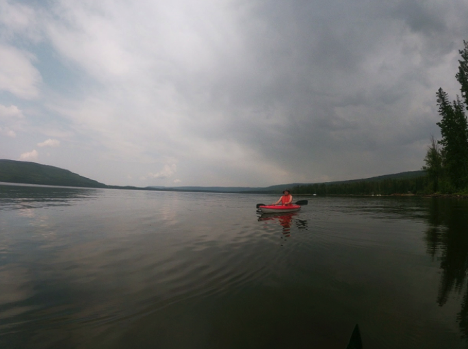 wide view of lake with one person kayaking