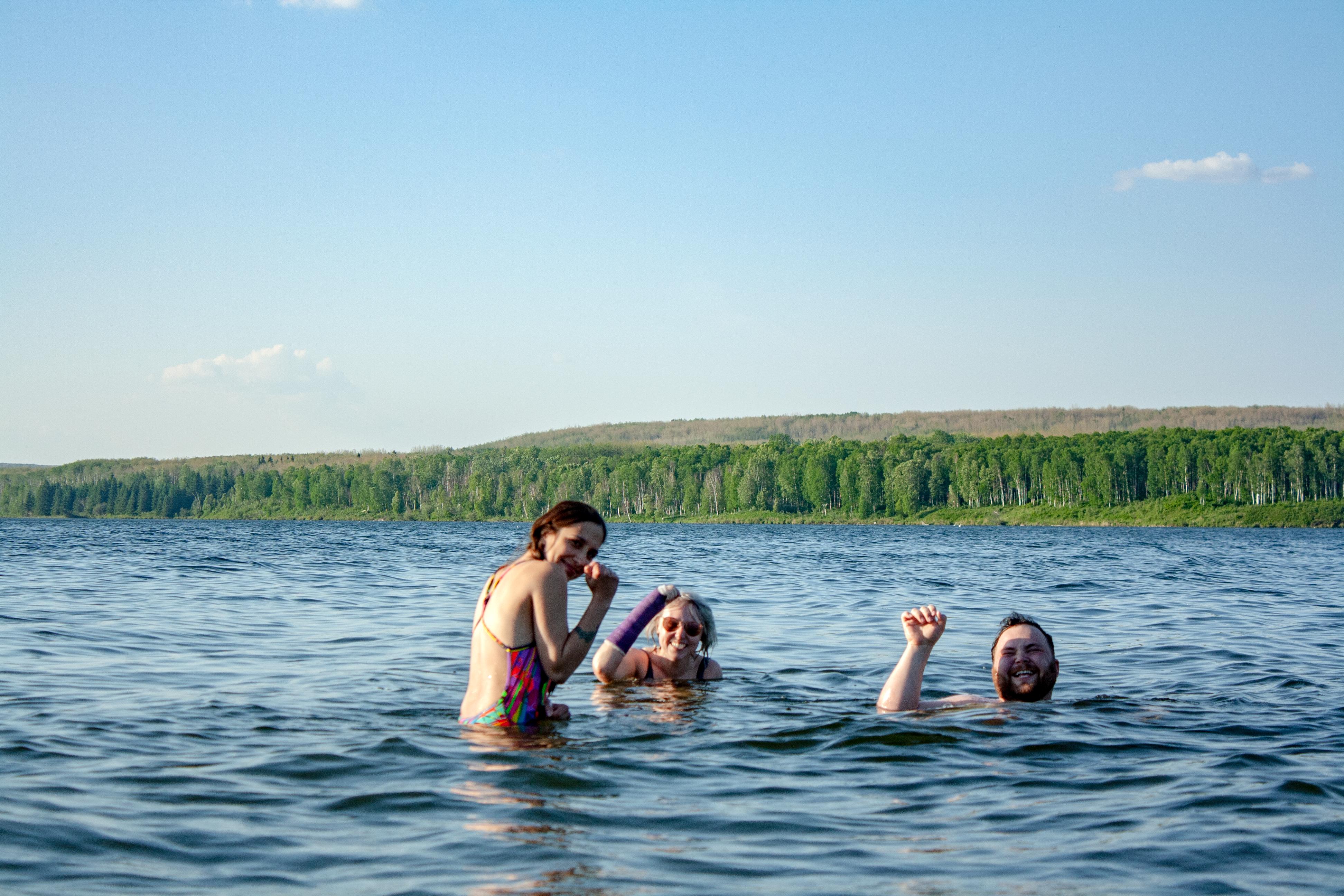 three friends swimming in lake