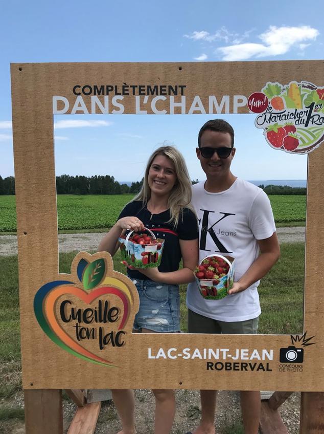 homme et femme tenant un panier de fraises