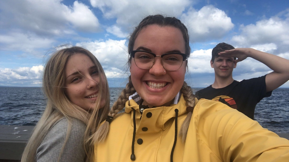 Photo of three young adults, by the lake.
