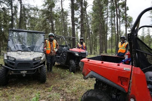 Group of friends standing with their UTV's.