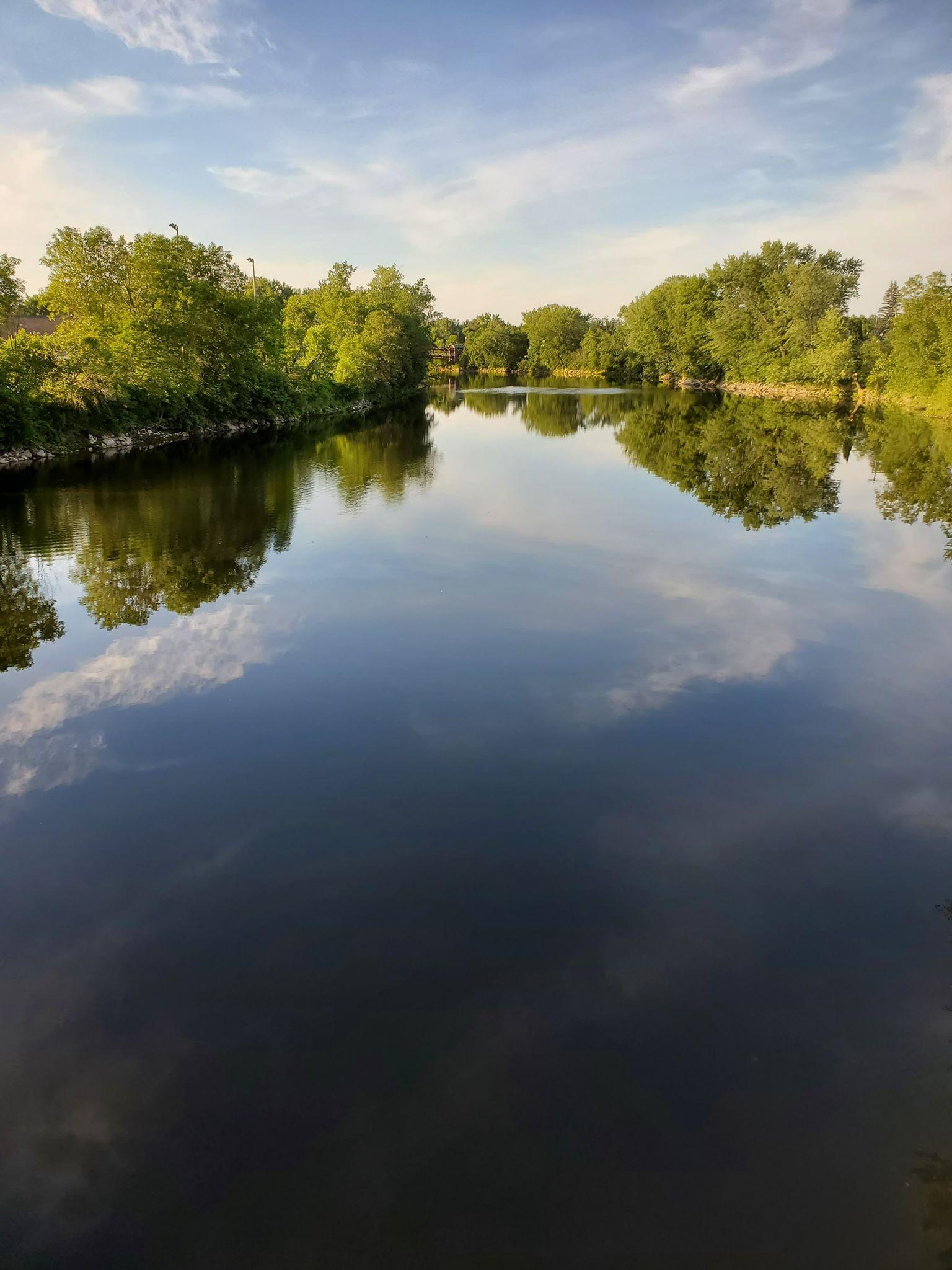 Reflets du ciel dans l'eau calme d'un lac.