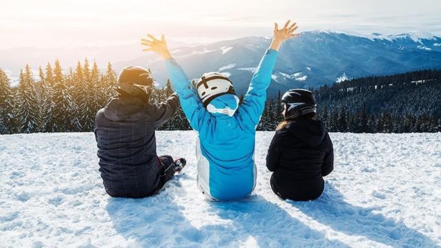 3 amis assis au sommet d'une piste de ski.